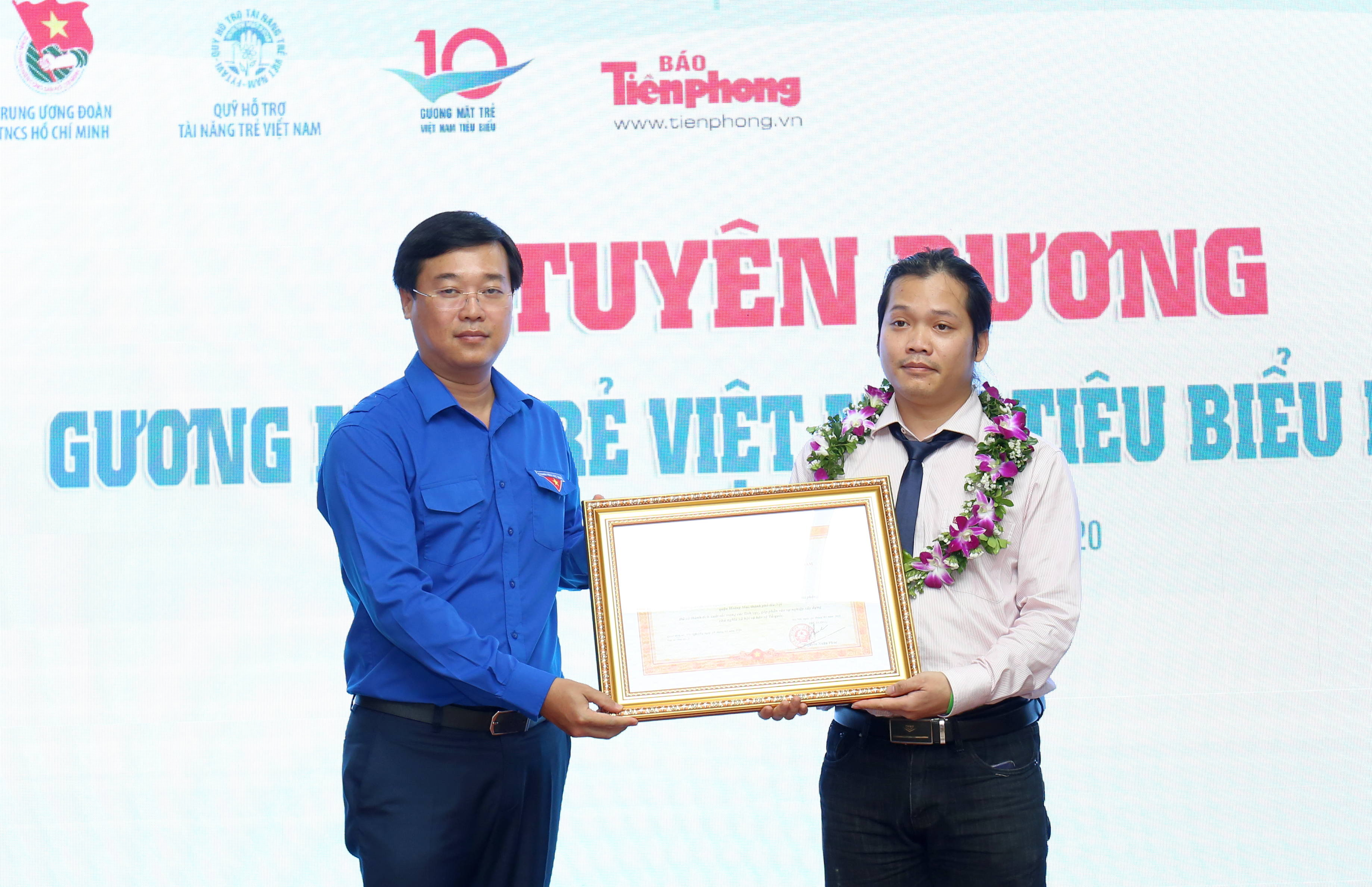 Mr. Le Quoc Phong awarding the Prime Minister's Certificate of Merit in Social activity field to Mr. Hoang Hoa Trung.
