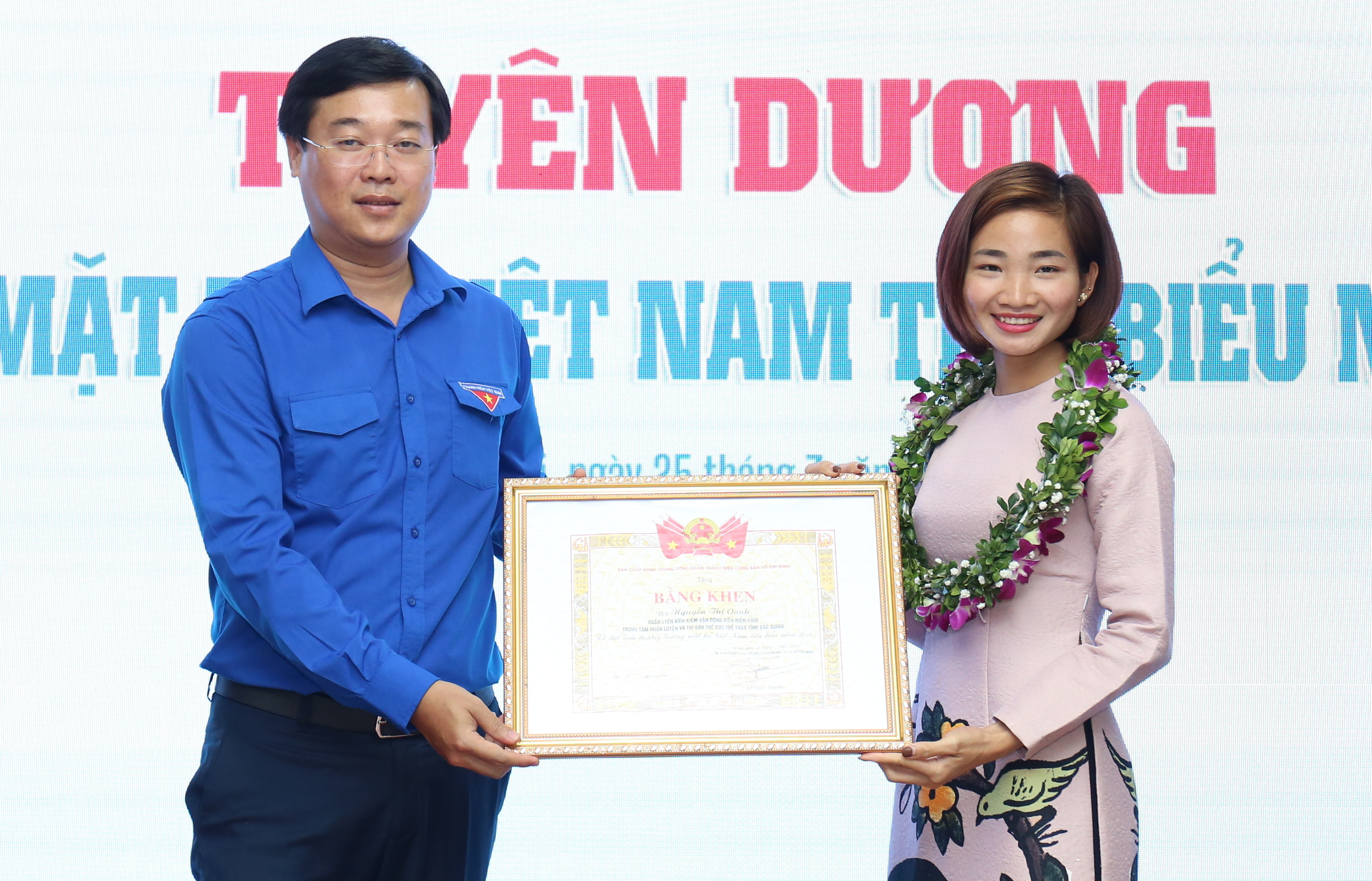 Mr. Le Quoc Phong giving the Prime Minister's Award of Merit to athlete Nguyen Thi Oanh