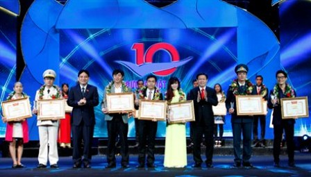 Politburo member and Head of the Central Economic Committee Vuong Dinh Hue and member of the Party Central Committee, First Secretary of the Ho Chi Minh Youth Union's Central Committee Nguyen Dac Vinh present the Vietnam Oustanding Young Face Award 2015 to the winners.
